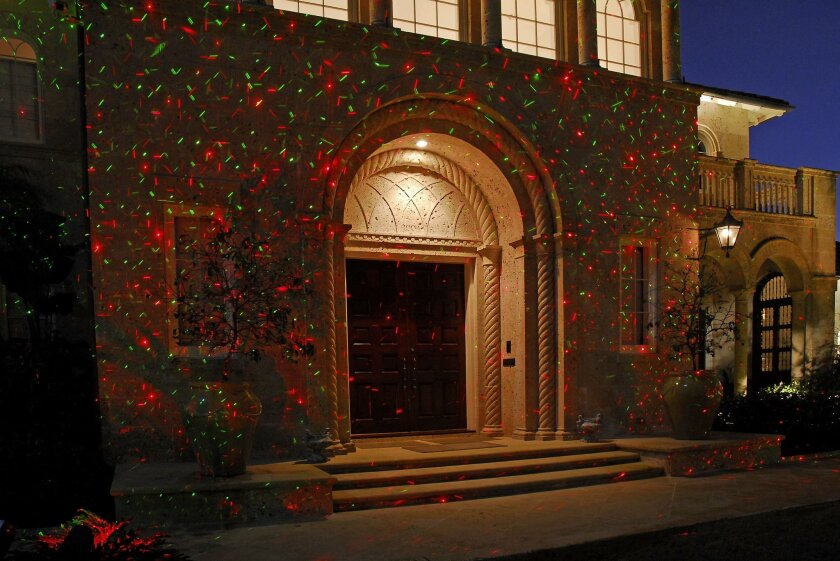 In this photo provided by Pinnacle Lighting Group, homeowners looking for something unique in holiday lighting can find it in projected laser lights. Using small spotlights, the technology shown in this photo provided by Pinnacle Lighting Group projects thousands of tiny pinpoints of red, green or red and green lights onto your home or any other hard surface. (AP Photo/Pinnacle Lighting Group)