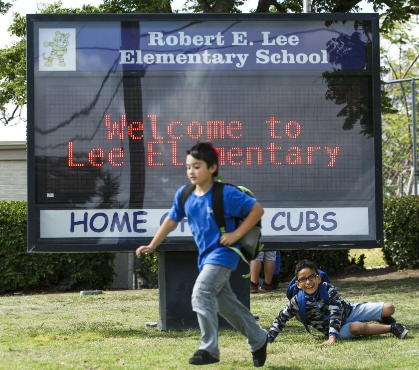 Several students play next to the electronic sign out in front of the soon-to-be-renamed Robert E. Lee Elementary School in San Diego.