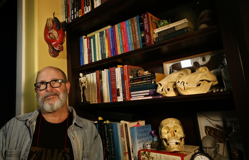 "Creator of ""Hellboy,"" Mike Mignola in his California studio, surrounded by books."