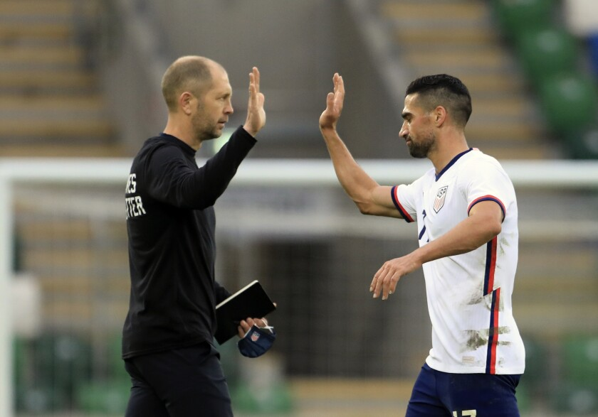 U.S. coach Gregg Berhalter, left, high-fives with U.S. midfielder Sebastian Lletget
