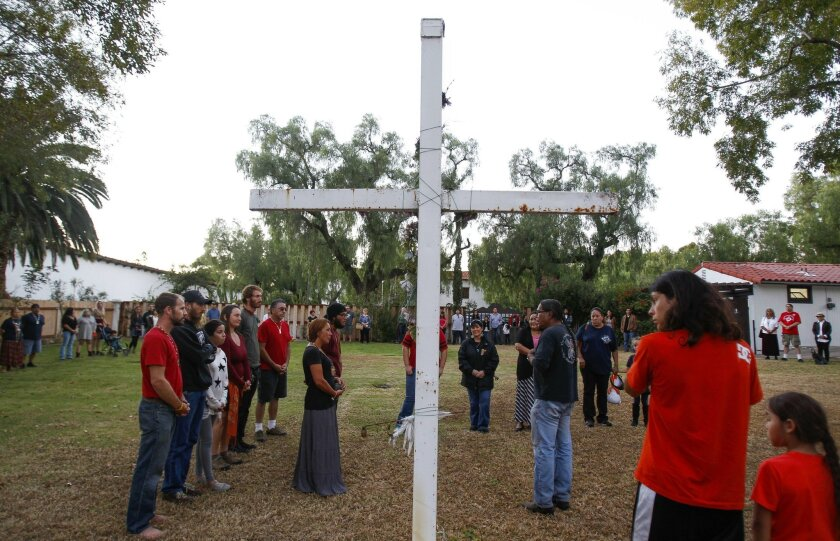 People, many of them Native Americans, stand during the Closing Ceremony for the Walk for the Ancestors at the Mission Basilica San Diego de Alcalá in San Diego on Saturday.