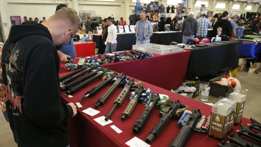 Gun enthusiasts check out semi-automatic rifle parts at a 2015 gun show at the Del Mar fairgrounds run by Crossroads of the West. The company runs shows across California, including those at the Ventura County fairgrounds.