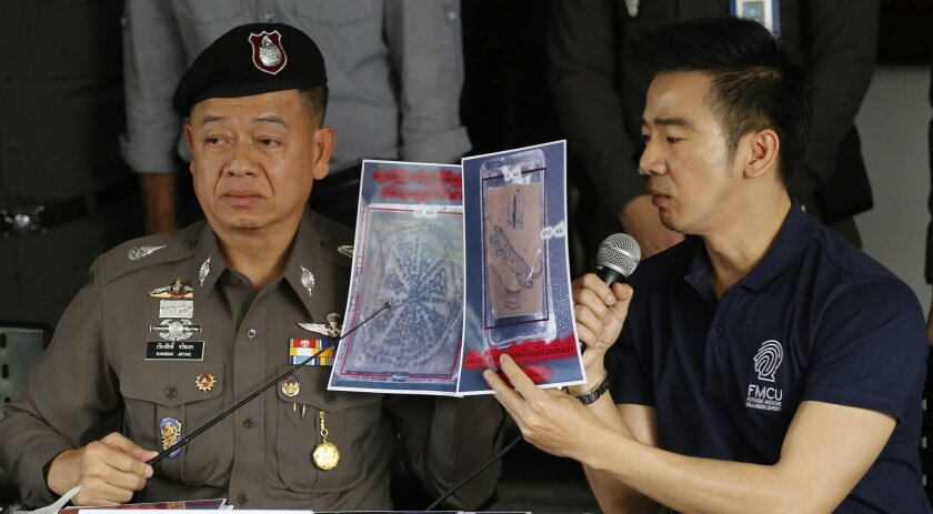 Thai police officers show pictures of a tattooed human skin during a press conference at Bangpongpang police station in Bangkok,Thailand,  Monday, Nov. 17, 2014. A shipping company in Bangkok put a trio of packages bound for the United States through a routine X-ray and made a startling discovery —