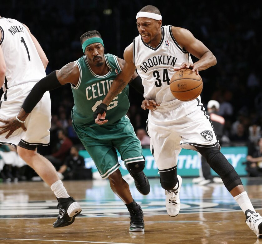 Brooklyn Nets forward Paul Pierce (34), playing with a protective brace on his injured right hand, drives around Boston Celtics forward Gerald Wallace (45) in the first half of their their NBA basketball game, Tuesday, Dec. 10, 2013, in New York. (AP Photo/Kathy Willens)