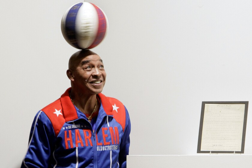 Curly Neal spins a ball on his head at an event in December 2010.