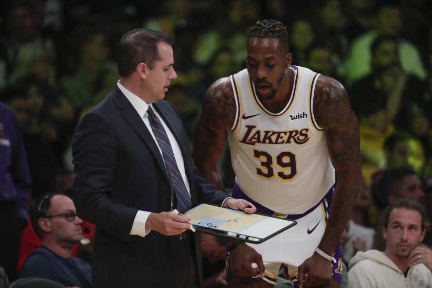 Coach Frank Vogel and veteran center Dwight Howard chat during a break in play during a game earlier this season.