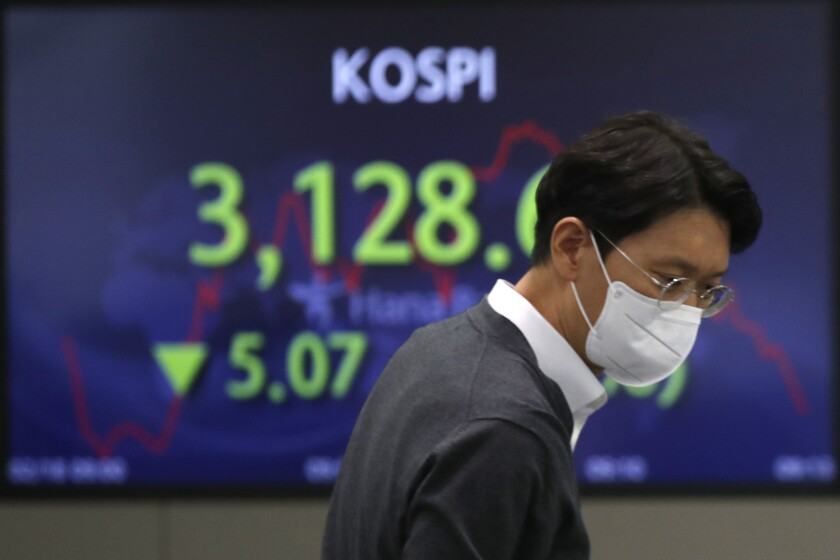 A currency trader walks near the screen showing the Korea Composite Stock Price Index (KOSPI), at the foreign exchange dealing room in Seoul, South Korea, Thursday, Feb. 18, 2021. Shares were mostly lower in Asia on Thursday after a mixed session on Wall Street as losses by technology and industrial companies offset other gains. (AP Photo/Lee Jin-man)