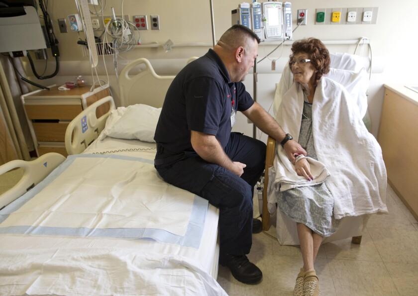 El paramédico Pete Amato, izquierda, platica con la paciente del hospital Stony Brook University, Melanie Chirichella, en su habitación, en Stony Brook, Nueva York. Amato manejó en medio de la tormenta de nieve el sábado para trasladar casi 32 kilómetros a Chirichella desde su casa hasta el hospital para que recibiera un trasplante de riñón, por el cual había esperado casi año y medio. (Foto AP/Julie Jacobson)