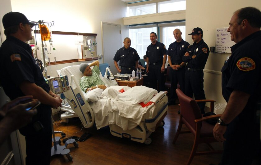 """Fellow San Diego firefighters surround Arsenio """"RC"""" Ortanez after he received his 20-year service pin at a ceremony Monday at UC San Diego Thornton Hospital. Ortanez is battling chronic myelogenous leukemia."""
