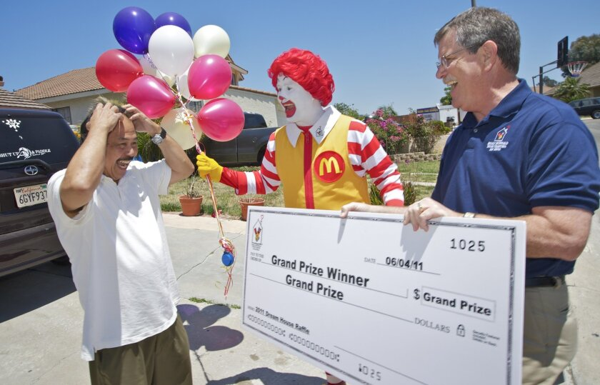 Amado Evangelista Jr. receives $1 million grand prize from Chuck Day, president and CEO of Ronald McDonald House Charities of San Diego.