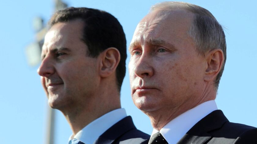 Syrian leader Bashar Assad, left, and Russian President Vladimir Putin watch troops march in Syria on Dec. 11, 2017.