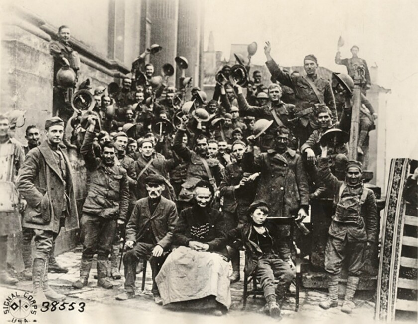 Nov. 11, 1918: Members of the 89th Infantry Division's 353rd Regiment, Company A, celebrate the end of World War I on church steps in Stenay, France.