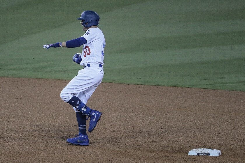 The Dodgers' Mookie Betts celebrates after hitting a two-run double against the Milwaukee Brewers on Oct. 1, 2020.