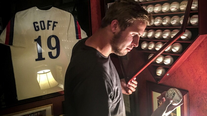 New Rams quarterbackJared Goff examines one of his father's mementosin the family's home in Novato, Calif., earlier this month.
