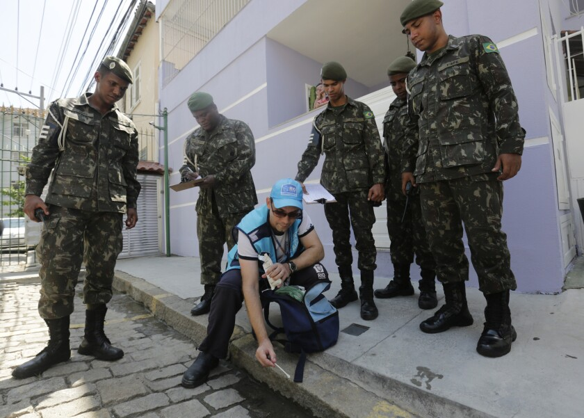 Surrounded by soldiers, a government health agent working in the Tijuca neighborhood of Rio de Janeiro uses larvicide to kill mosquitos that spread the Zika virus.