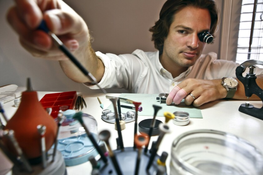 Cameron Weiss reaches for a screwdriver while assembling a watch at his workbench in his apartment in Beverly Hills.