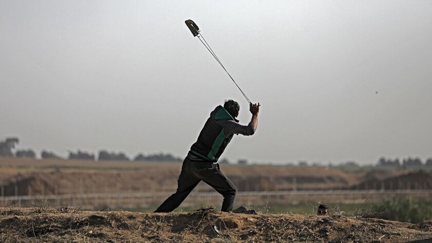 A Palestinian protester hurls stones during clashes with Israeli troops along the border between Israel and the Gaza Strip on March 31.