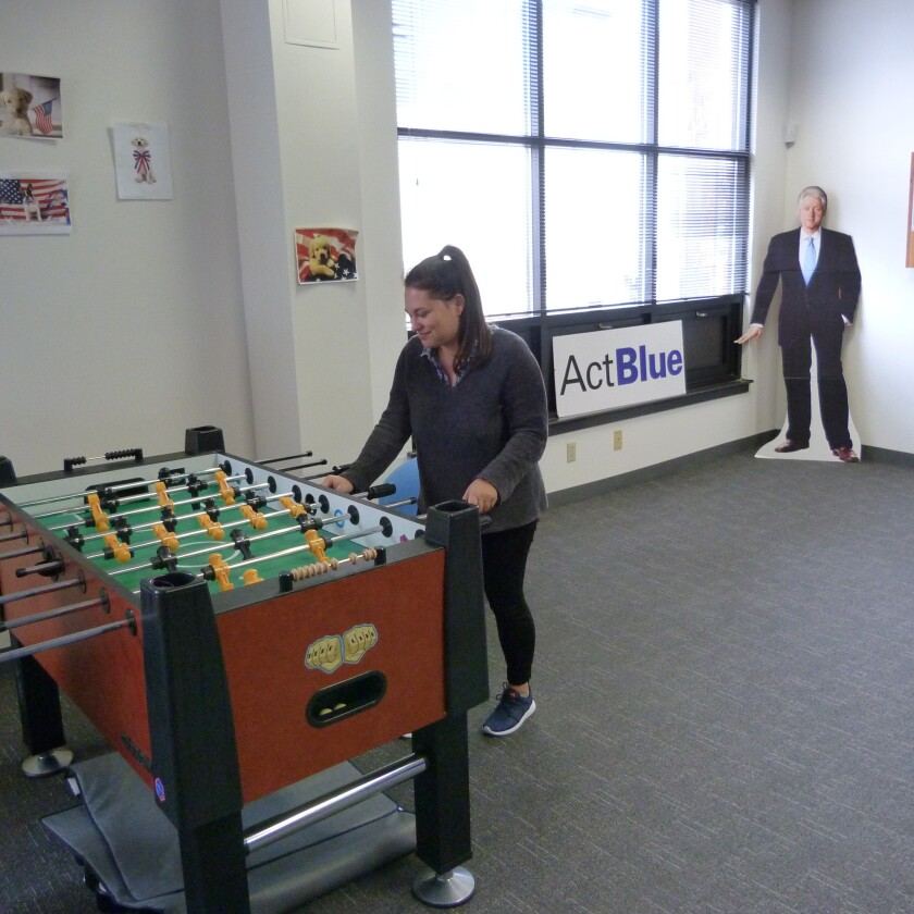 Marketing manager Hannah Brown hits the foosballl table in the game room at ActBlue's Somerville, Mass., headquarters. Behind her is a cardboard cutout of Bill Clinton.