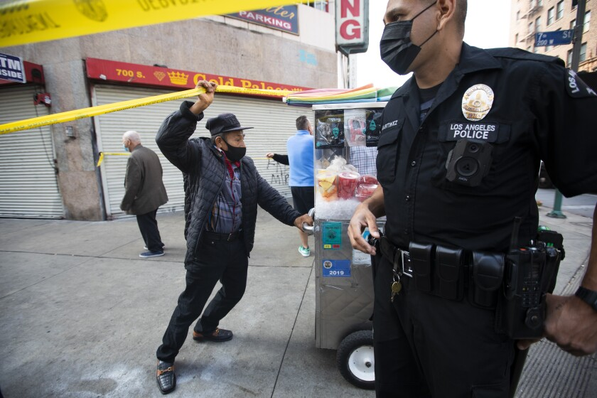 A vendor moves his pushcart as an LAPD officer clears the corner of South Broadway and 7th Street of pedestrians.