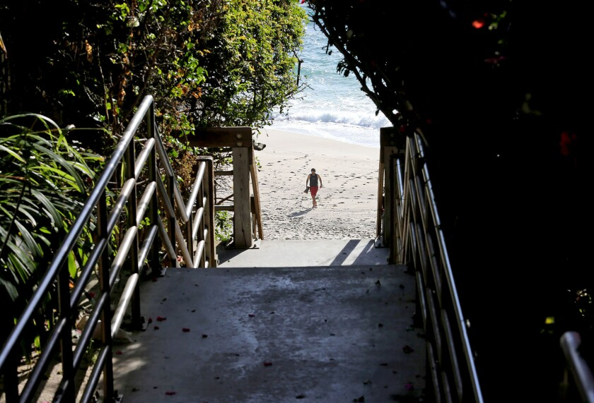 A beachgoer approaches the stairs on the sand at Table Rock Beach in South Laguna.