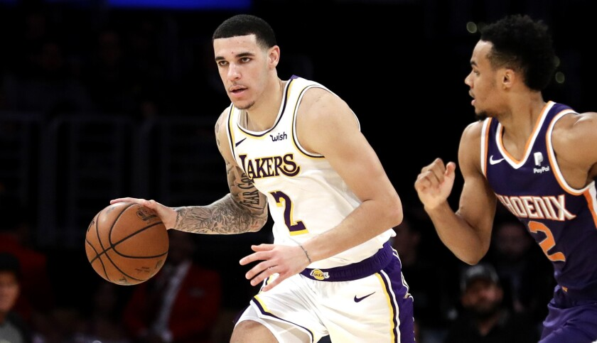 Los Angeles Lakers' Lonzo Ball, left, dribbles up court next to Phoenix Suns' Elie Okobo during the