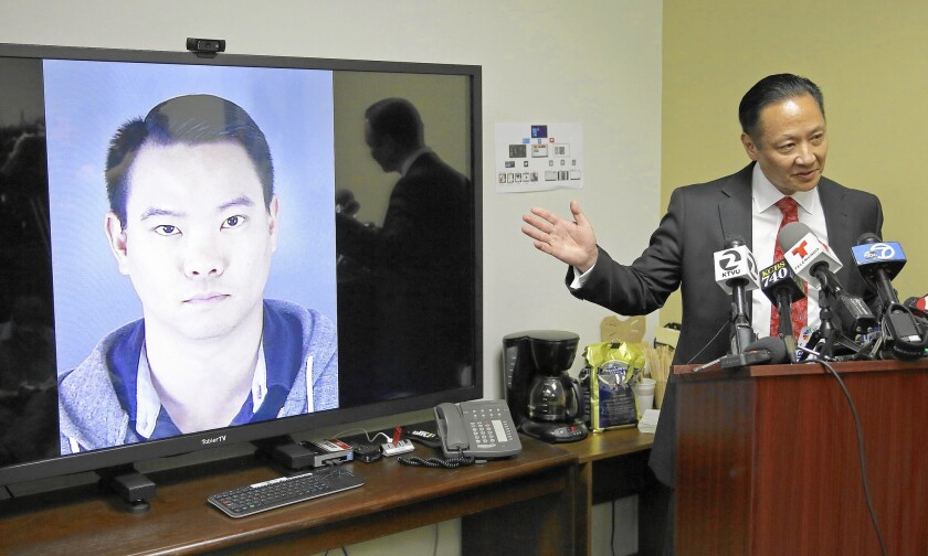 San Francisco Public Defender Jeff Adachi stands near a picture of city Police Officer Jason Lai -- who Adachi says wrote text messages disparaging blacks, Latinos and others -- during a news conference.