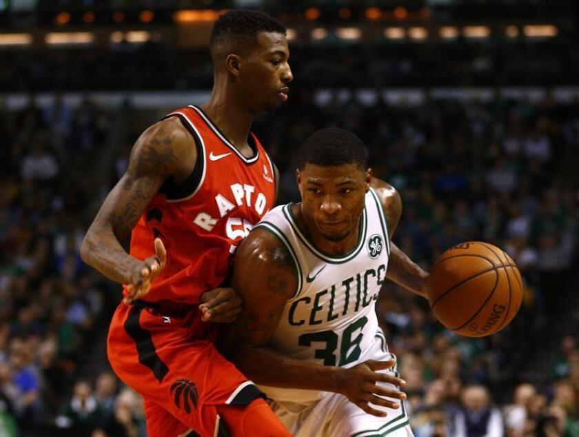 Marcus Smart (d), guardia de los Celtics de Boston, fue registrado este domingo al intentar superar la marca de Delon Wright (i), de los Raptors de Toronto, durante un partido de la NBA, en el TD Garden de Boston (Massachusetts, EE,UU.) EFE