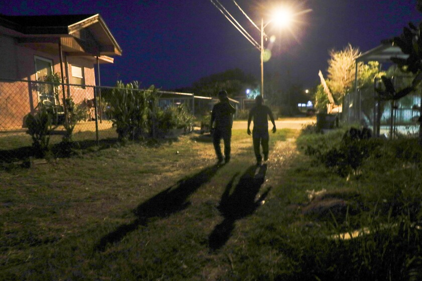 Two men suspected of crossing the border illegally search for a safe house in the early morning darkness in Colonia De La Cruz. After speaking briefly to a journalist, they turned around in apparent confusion and headed back down the alley.
