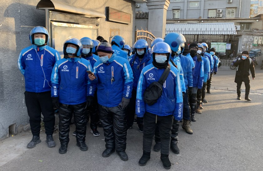 Men, wearing masks and matching clothing and helmets, stand in line outside a city building.