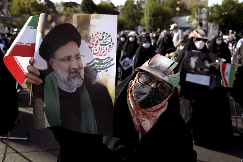 Supporter holding poster of Iranian presidential candidate Ebrahim Raisi