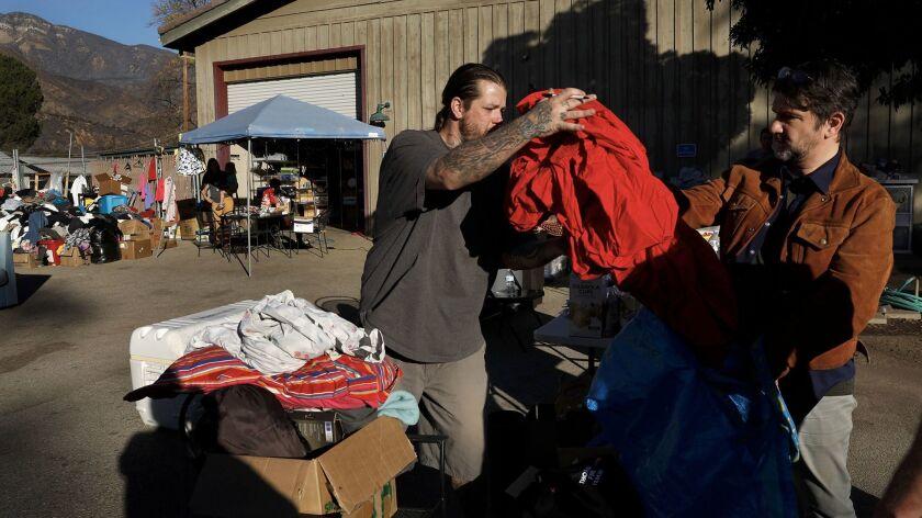 OJAI, CA-DECEMBER 28, 2017: Volunteer Jason Estrada, left, receives donated items, including bed sh