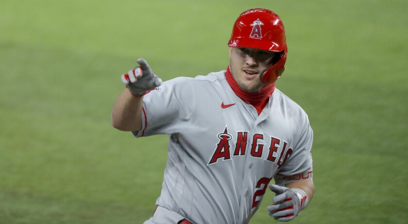 The Angels' Mike Trout points to the dugout after hitting a two-run homer against the Texas Rangers on Aug. 7, 2020.