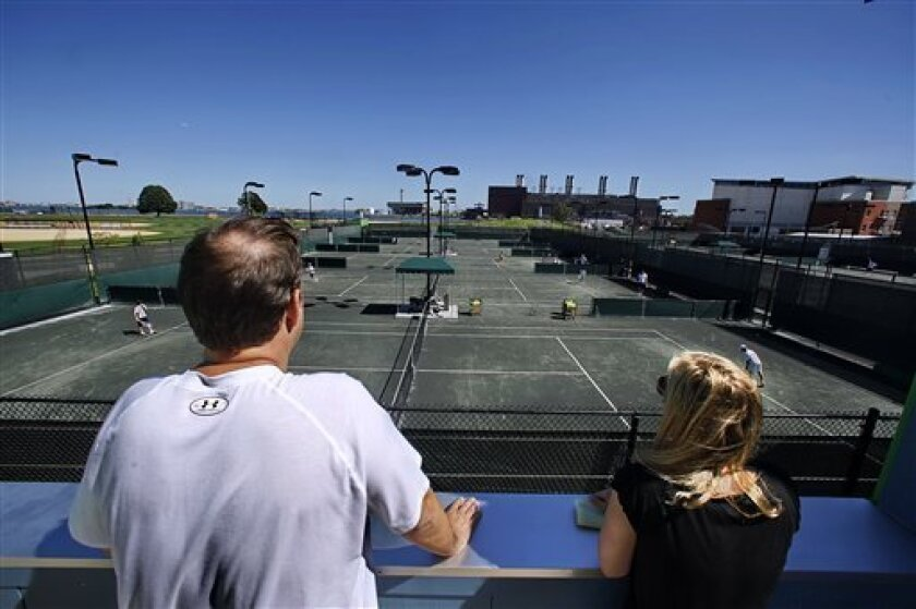 In this Aug. 27, 2010 photo, Mitchell and Caroline Nussbaum, from Scarsdale, N.Y., watch from an overlook as their son Andrew, 10, trains at the John McEnroe Tennis Academy in New York. The academy will officially welcome its first class, including the young Nussbaum, who will make at least two trips weekly from his suburban home to the revamped, 20-court, $18 million tennis complex on Randall's Island. (AP Photo/Bebeto Matthews)