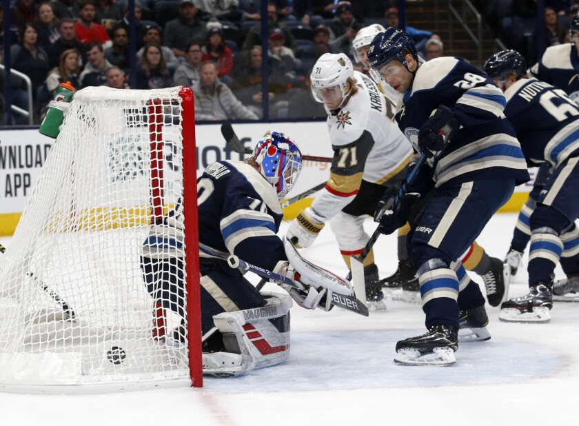 Vegas Golden Knights forward William Karlsson, center, of Sweden, watches forward Reilly Smith's goal past Columbus Blue Jackets goalie Joonas Korpisalo, left, of Finland, as forward Oliver Bjorkstrand, of Denmark, defends during the first period of an NHL hockey game in Columbus, Ohio, Tuesday, Nov. 5, 2019. (AP Photo/Paul Vernon)