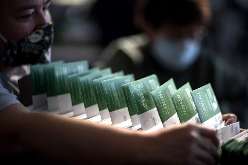 An election inspector checks the names of voters on ballots.