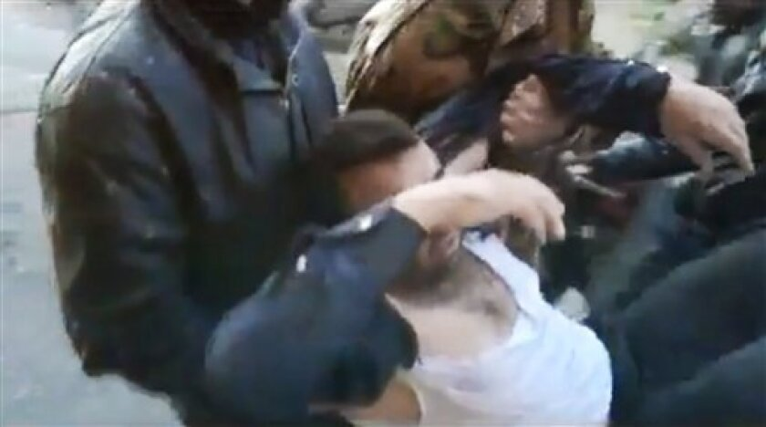 This image made from amateur video and released by Shaam News Network Tuesday, March 27, 2012, purports to show a Syrians carrying a wounded man in Homs, Syria. Syrian activists said Wednesday a government offensive in northern Syria during which troops overran a major opposition stronghold has left behind scenes of destruction, with corpses in the streets, homes burned to the ground and shops that have been pillaged and looted. (AP Photo/Shaam News Network via APTN) THE ASSOCIATED PRESS CANNOT INDEPENDENTLY VERIFY THE CONTENT, DATE, LOCATION OR AUTHENTICITY OF THIS MATERIAL. TV OUT