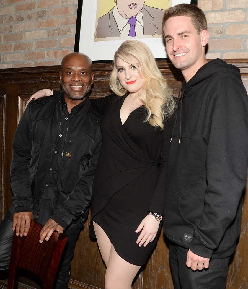 Snapchat Chief Executive Evan Spiegel, right, is photographed with Epic Records Chairman and Chief Executive L.A. Reid and singer Meghan Trainor at Epic's Grammy Awards party in West Hollywood on Feb. 6.