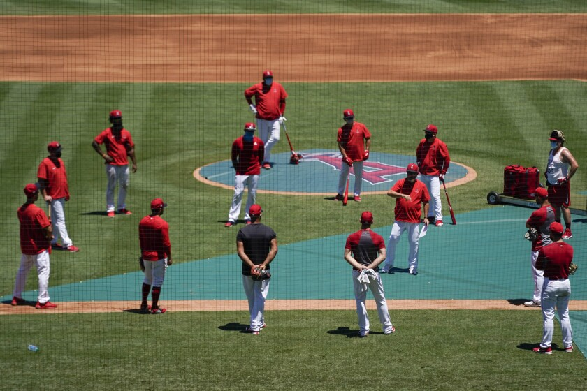 Angels manager Joe Maddon meets with his players on the field at Angel Stadium.