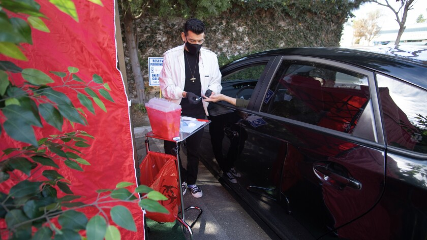 Manny Muroworks administers HIV testing in a drive-through setup.