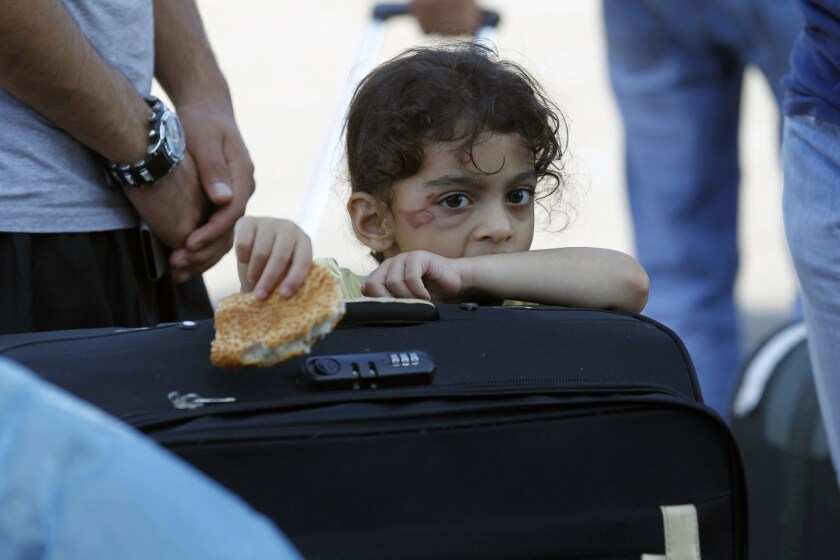 A Palestinian girl waits at the Rafah border terminal in the southern Gaza Strip to cross into neighboring Egypt after the crossing was opened for humanitarian reasons.