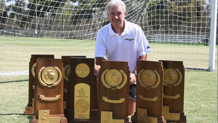 Former UCSD women's soccer coach Brian McManus, in a 2009 file photo posing with trophies from his seven Div. II or III national championships.