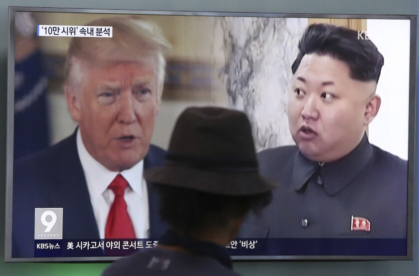 In this Aug. 10, 2017, photo, a man watches a television screen showing U.S. President Donald Trump and North Korean leader Kim Jong Un during a news program at the Seoul Train Station in Seoul, South Korea.