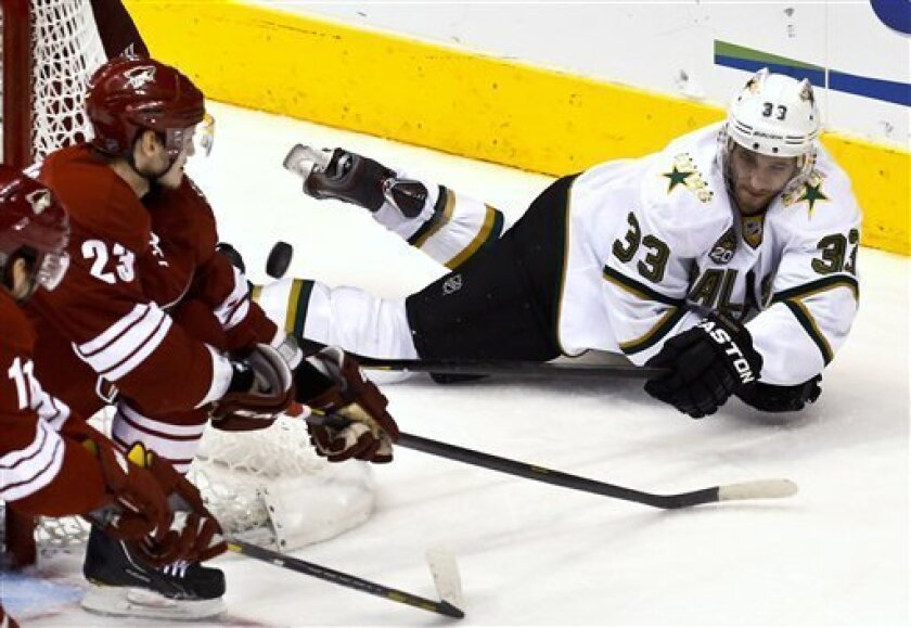 Dallas Stars' Alex Goligoski (33) gets a shot off as he falls down in front of Phoenix Coyotes' Oliver Ekman-Larsson (23), of Sweden, and Martin Hanzal (11), of the Czech Republic, in the second period during an NHL hockey game on Saturday, March 9, 2013, in Glendale, Ariz. (AP Photo/Ross D. Frankl