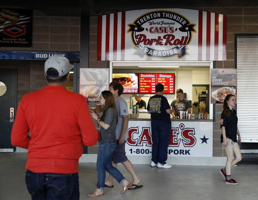 In this Wednesday, May 25, 2016 photograph, customers buy food at a Case's Pork Roll Paradise vendor during a Trenton Thunder baseball game in Trenton, N.J. The salted pork-based processed meat was developed in the state's capital city of Trenton by John Taylor in 1856. It's often consumed as a breakfast meat paired with egg and cheese in a sandwich usually served on a bagel, bun or hard roll. (AP Photo/Mel Evans)