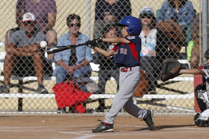 Costa Mesa American Little League's Jordan Lee bats a single against Costa Mesa National in the Dist