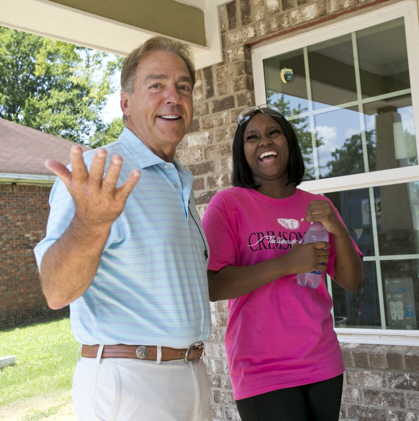 Twelve Alabama football players along with Coach Nick Saban and members of the staff helped with construction on the Habitat for Humanity Tuscaloosa's 18th Championship House funded by the Nick's Kids Foundation Tuesday, July 27, 2021, in Tuscaloosa, Alabama. Saban and homeowner Joselyn Hamner share a laugh on the front porch of her new house. (Gary Cosby Jr./The Tuscaloosa News via AP)