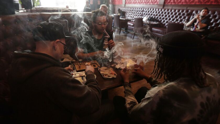 Customers smoke marijuana in the smoking lounge at Barbary Coast Collective in San Francisco. The city plans to issue more permits for marijuana lounges this year.