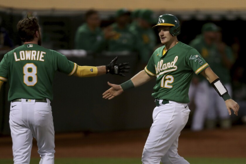 Oakland Athletics' Sean Murphy, right, is congratulated by Jed Lowrie, left, after both scored on a double by Elvis Andrus against the Los Angeles Angels during the sixth inning of a baseball game in Oakland, Calif., Tuesday, June 15, 2021. (AP Photo/Jed Jacobsohn)