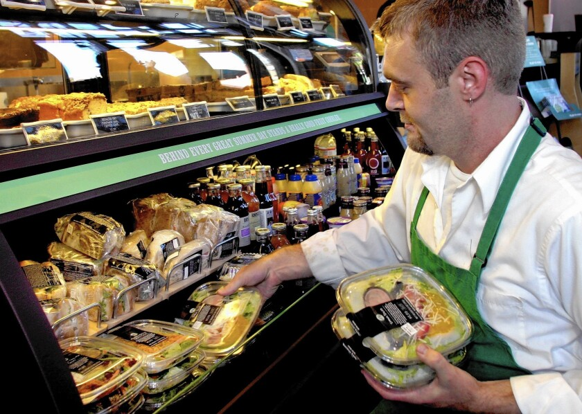 Adam Greener stocks a refrigerated case of sandwiches, salads and cold drinks at a Starbucks store in Denver in 2004. The company has announced that it intends to donate all its leftover food to charity.