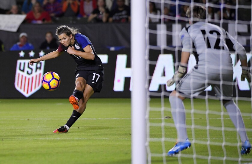 United States midfielder Tobin Heath, left, kicks toward the goal as Romania goalkeeper Roxana Oprea defends during the first half on Nov. 13.